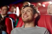 Happy young man watching movie in theater — Stock Photo