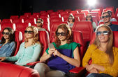 Happy woman with smartphone in 3d movie theater — Stock Photo