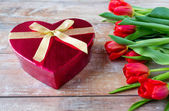 Close up of red tulips and chocolate box — Stock Photo