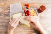 Close up of woman with food in plastic container — Stock Photo