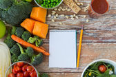 Close up of ripe vegetables and notebook on table — Stock Photo
