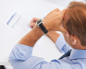 Stressed man filling tax form — Stock Photo