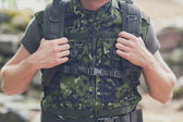 Close up of young soldier with backpack in forest — Stock Photo