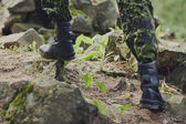 Close up of soldier climbing on rocks in forest — Stock Photo