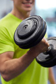 Close up of smiling man with dumbbell in gym — Stock Photo
