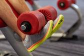Close up of man legs exercising on gym machine — Stock Photo