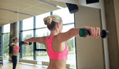 Woman with dumbbells flexing muscles in gym — Stock Photo
