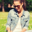 Smiling young girl with notebook writing in park — Stock Photo #70399729