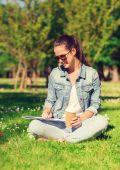 ノートブックとコーヒーのカップを持つ若い女の子の笑顔 — ストック写真