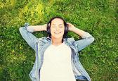 Jovem sorridente em fones de ouvido deitado na grama — Fotografia Stock
