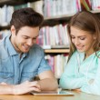 Happy students with tablet pc in library — Stock Photo #70586037