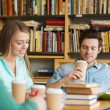 Students reading and drinking coffee in library — Stock Photo #70586079