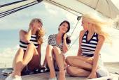 Smiling girlfriends sitting on yacht deck — Stock Photo