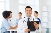 Happy doctor with clipboard over medical team — Stock Photo