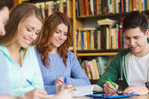 Happy students writing to notebooks in library — Stock Photo