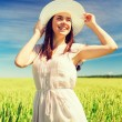 Smiling young woman in straw hat on cereal field — Foto Stock #70772915