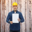 Smiling male builder in helmet with clipboard — Stock Photo #70774987