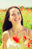 Laughing young woman on poppy field — Stock Photo