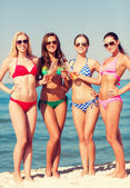 Group of smiling young women drinking on beach — Stock Photo