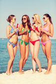 Group of smiling women eating ice cream on beach — Stock Photo