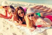 Group of smiling women with smartphone on beach — Stock Photo