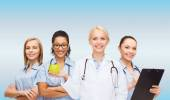 Smiling female doctor and nurses with green apple — Stock Photo