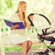 Happy mother with book and stroller in park — Stock Photo #70914781