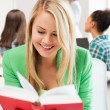 Smiling student girl reading book at school — Stock Photo #70916527