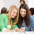 Student girls pointing at notebook at school — Stock Photo #70916619