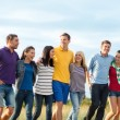 Group of happy friends walking along beach — Stock Photo #70917215