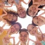 grupp leende tonåringar visar tecken på seger — Stockfoto #70917447