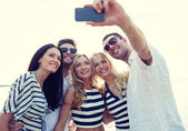Happy friends on beach and taking selfie — Stock Photo