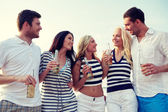 Smiling friends with drinks in bottles on beach — Stock Photo