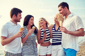 Friends eating ice cream and talking on beach — Stock Photo