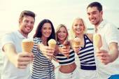Smiling friends eating ice cream on beach — Stock Photo
