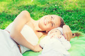 Happy mother lying with little baby on blanket — Stock Photo
