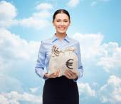 Businesswoman holding money bags with euro — Stock Photo