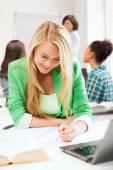 Chica estudiante escribir en cuaderno en la escuela — Foto de Stock