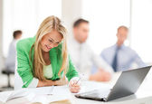 Attractive businesswoman taking notes in office — Stock Photo