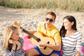 Group of happy friends playing guitar on beach — Stock Photo