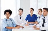 Group of happy doctors on conference at hospital — Stock Photo