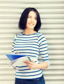 Adolescente feliz e sorridente com o bloco de notas grande — Fotografia Stock