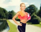 Smiling sporty woman with water bottle and towel — Stock Photo