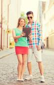 Smiling couple with tablet pc in city — Stock Photo