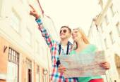 Smiling couple with map and photo camera in city — Stock Photo