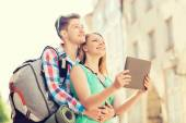 Smiling couple with tablet pc and backpack in city — Stock Photo