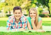 Smiling couple lying on blanket in park — Stock Photo