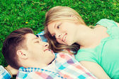 Smiling couple lying on grass in park — Stock Photo