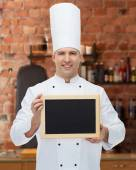Happy male chef cook holding blank menu board — Stock Photo