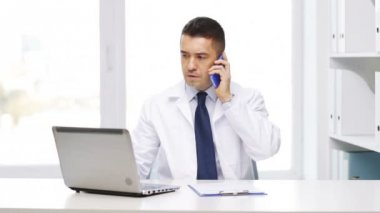 Doctor with laptop calling on smartphone — Stock Video